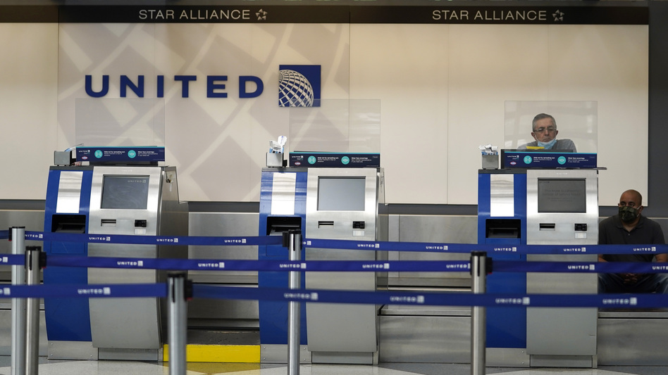 United Airlines employees work at ticket counters at Chicago's O'Hare International Airport on Oct. 14. United and other airline stocks have been hard-hit by the pandemic economic slowdown. (Nam Y. Huh/AP)