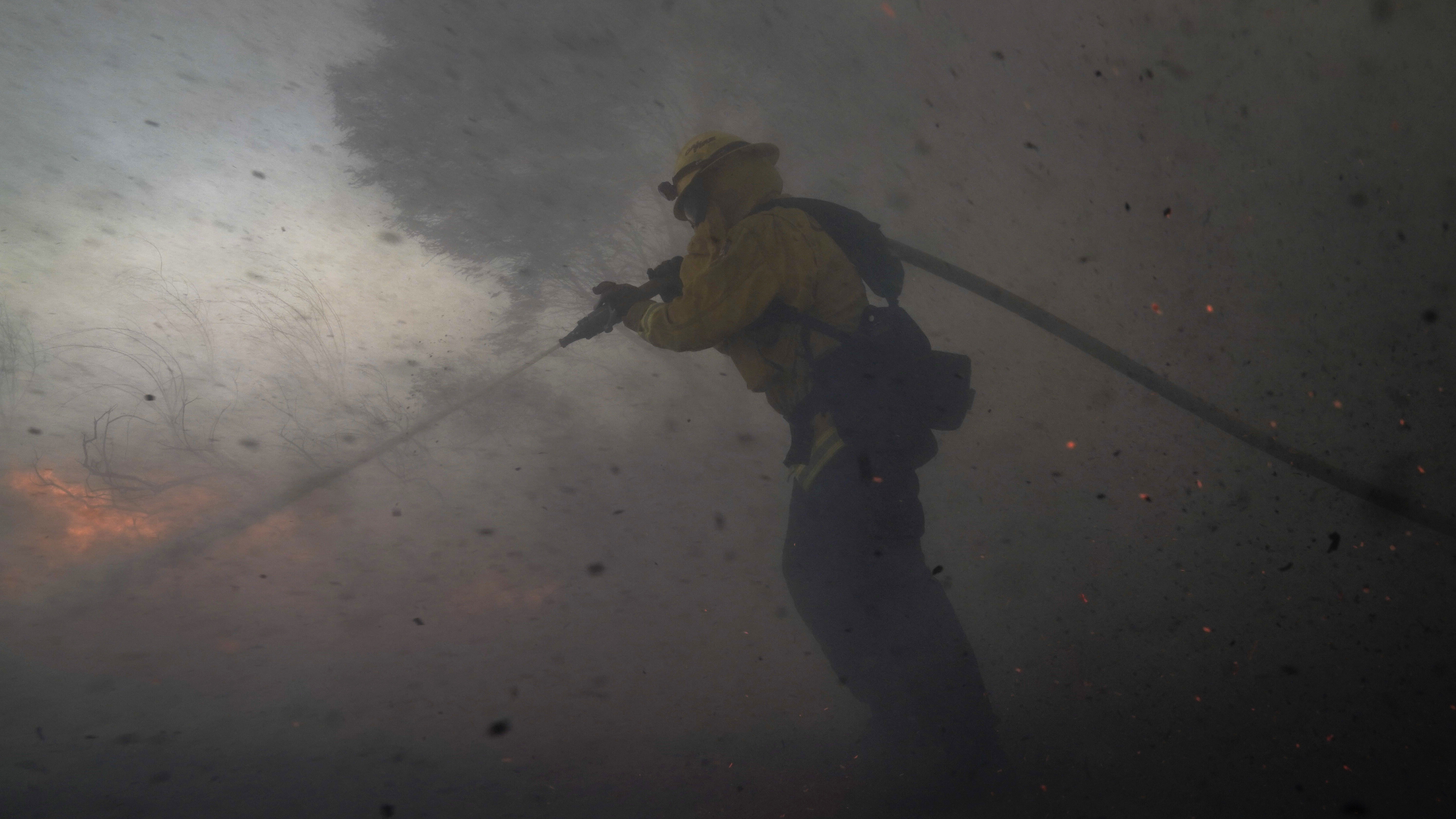 A firefighter battles the Silverado Fire Monday,in Irvine, Calif. The wildfire forced evacuation orders for 60,000 people in Southern California.