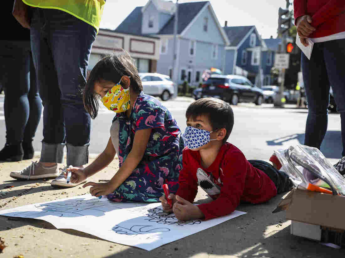BOSTON, MA - OCTOBER 10: Children work on a sign during a protest in Boston's Dorchester on Oct. 10, 2020.