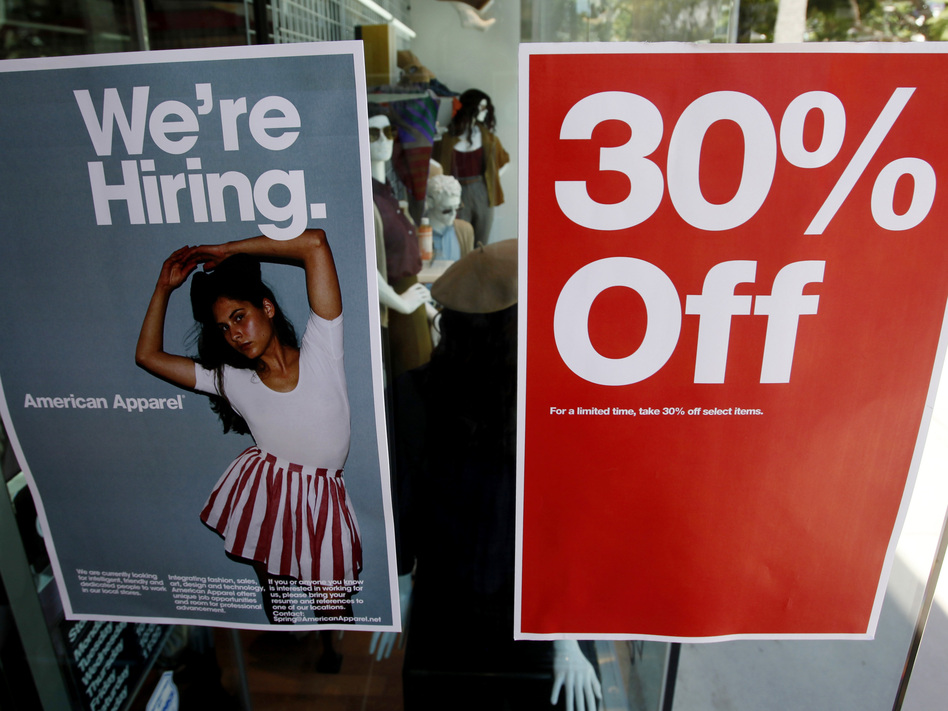 Signs in the window of a retail store offers discounts, and jobs, in Santa Monica, Calif. U.S. GDP grew at a record-setting rate, reflecting pent-up activity after the coronavirus lockdowns, but economists warn of trouble ahead. (Reed Saxon/Associated Press)