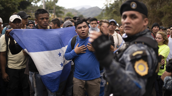 Honduran migrants walking in a group stop before Guatemalan police in January near Agua Caliente, Guatemala. The Democratic staff of the Senate Foreign Relations Committee says U.S. immigration agents in Guatemala helped officials deport Hondurans traveling in a migrant caravan earlier this year.