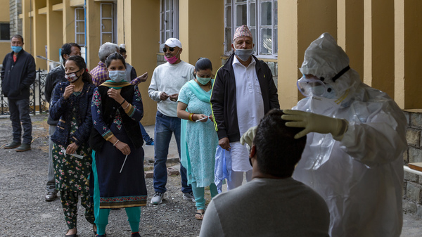 A health officer in protective suit collects a swab sample to be tested for coronavirus on Thursday in Dharmsala, India. India