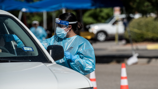 A nurse conducts a coronavirus test at a newly opened mega drive-through site at El Paso Community College Valle Verde campus on July 21 in El Paso, Texas.