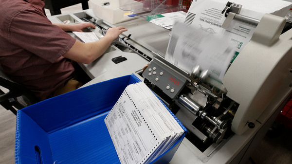 An election worker opens envelopes and removes ballots so they can be counted at the election office on Octo. 26, 2020 in Provo, Utah.