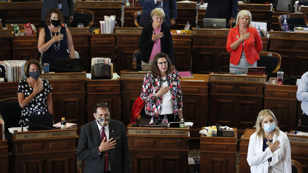 State Representatives stand at their desks during the Pledge of Allegiance in the Iowa House chambers in Des Moines, Iowa, in June.