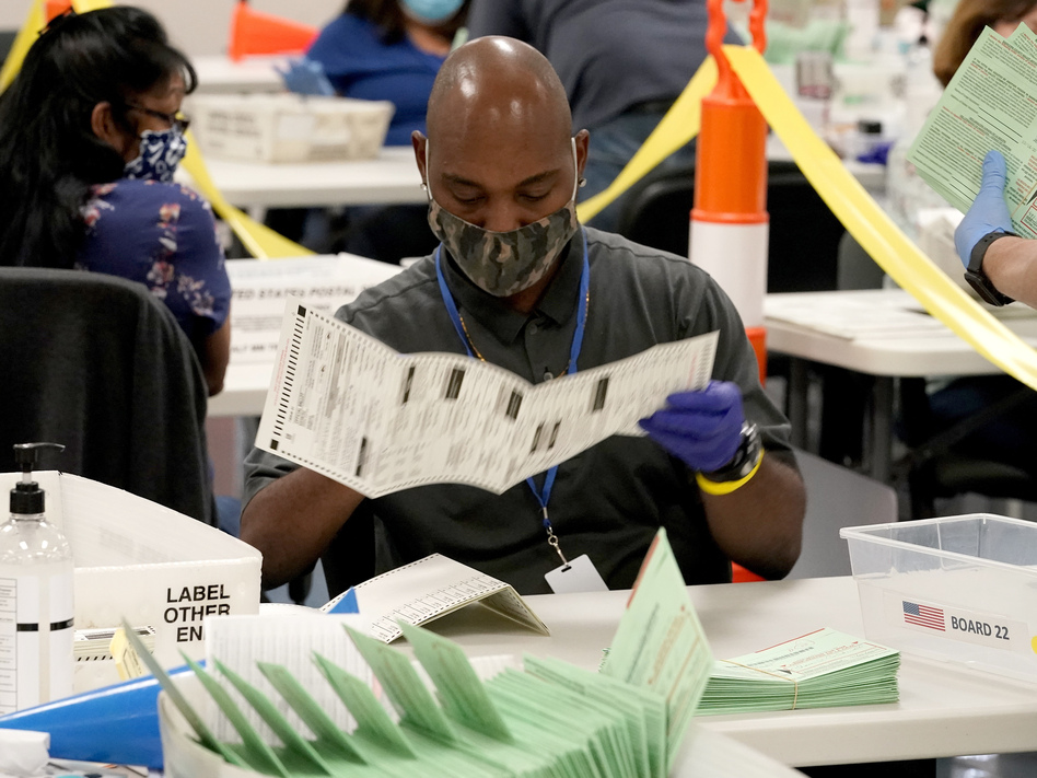 Election workers sort ballots at the Maricopa County Recorder's Office in Phoenix. Mail-in ballots in Arizona are already being counted. (Matt York/AP)