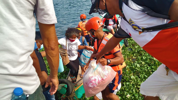 In this photo provided by the Philippine Coast Guard, families are evacuated by members of the Philippine Coast Guard to safer ground in Camarines Sur province as they prepare for typhoon Goni. Families living near coastal towns have moved to evacuation centers as the strong typhoon nears.