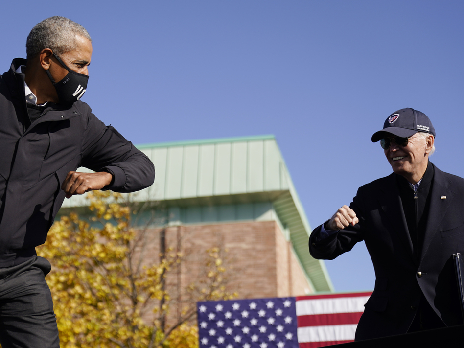 Democratic presidential nominee Joe Biden and former President Barack Obama greet each other at a drive-in rally in Flint, Mich. (Andrew Harnik/AP)
