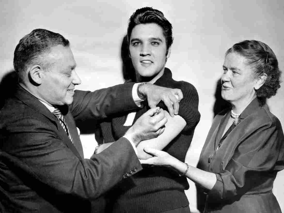 UNITED STATES - OCTOBER 28: Elvis Presley receiving a polio vaccination from Dr. Leona Baumgartner and Dr. Harold Fuerst at CBS studio 50 in New York City. (Photo by Seymour Wally/NY Daily News Archive via Getty Images)