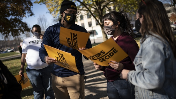 """People gather with signs that read """"Voters Decide"""" at the Civic Center Park while waiting for the results of election in Kenosha, Wis. on Wednesday."""