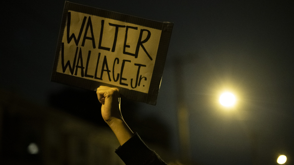 """A demonstrator holds a placard reading """"WALTER WALLACE JR."""" during a protest near the location where Walter Wallace, Jr. was killed by two police officers on Oct, 27 in Philadelphia."""