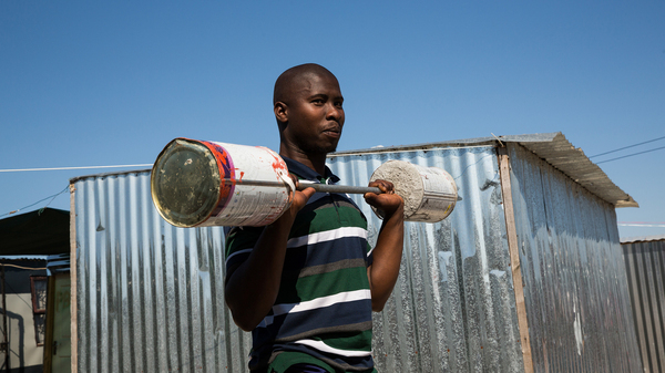 Alfred Sonandi plays around with a makeshift barbell — concrete poured into two tins on either end of a stick. People in the settlement of Covid don