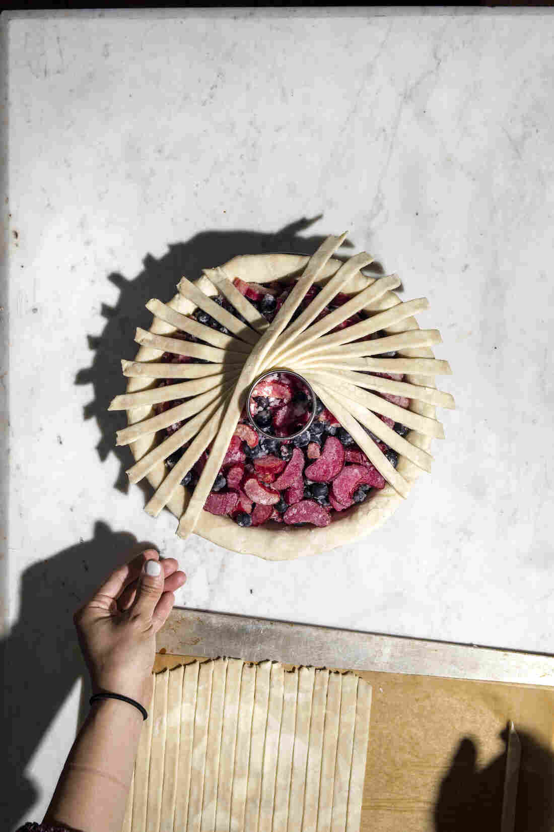 Continue laying dough strips in this fashion, working your way around the pie surface twice. Resist the urge to manually curve each strip. The optical illusion of the full design inspires a curved effect, but the individual strips should be maintained as straight lines.