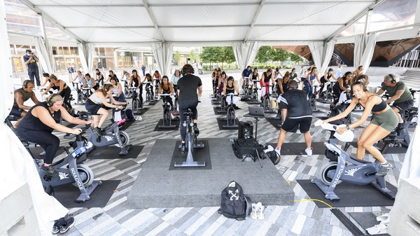 People attend an spin class under an outdoor tent in New York City.