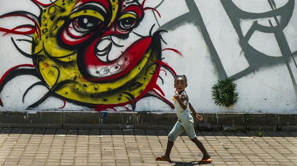 A child walks past a COVID-19 graffiti in Soweto
