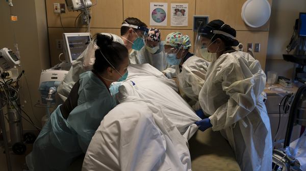 Medical personnel treat a COVID-19 patient at Providence Holy Cross Medical Center in Los Angeles on Thursday. California is imposing an overnight curfew on most residents to blunt a surge in coronavirus infections.