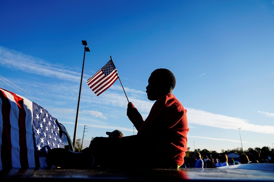 Xavier Watts, 9, waves an American flag during a campaign rally for Georgia Democratic U.S. Senate candidates Jon Ossoff and Raphael Warnock on Nov. 15 in Marietta, Ga. (Brynn Anderson/AP)