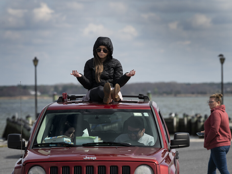 A member of Jesus' Church prays on top of a car during a Sunday church service held at Great Marsh Park in Cambridge, Maryland, on March 22, 2020. (JIM WATSON/AFP via Getty Images)