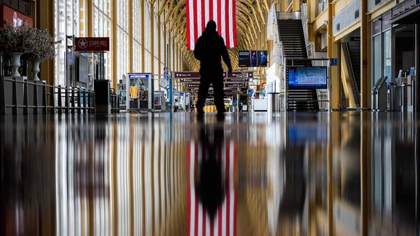 An airport employee, seen earlier this year, walks through Reagan National Airport in Arlington, Va. On Thursday, the Centers for Disease Control and Prevention warned that Americans should refrain from traveling for the upcoming holiday.