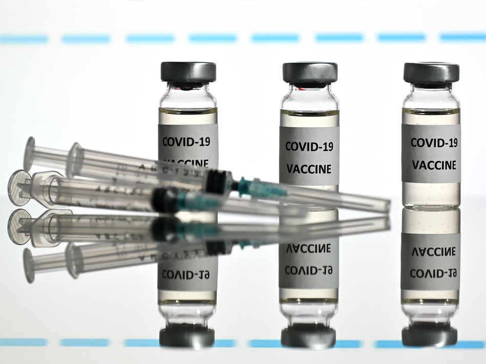 An illustration picture shows vials with COVID-19 vaccine stickers attached and syringes with the logo of U.S. biotechnology company Moderna on November 17. (Justin Tallis/AFP via Getty Images)