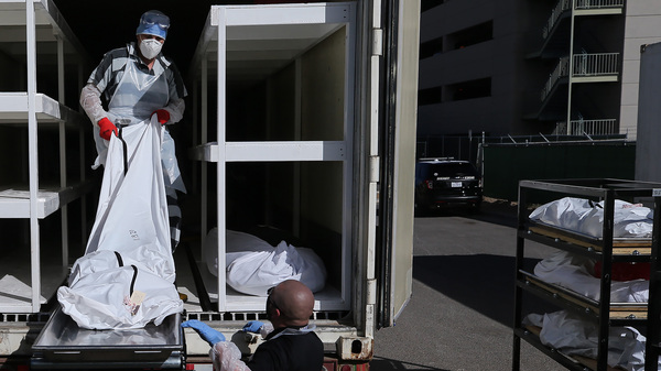A low-level inmate from El Paso County detention facility works loading bodies wrapped in plastic into a refrigerated temporary morgue trailer in a parking lot of the El Paso County Medical Examiner