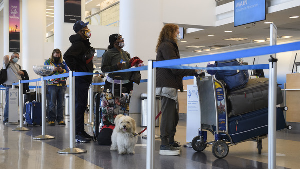 Travelers wait to check baggage for an American Airlines flight at Los Angeles International Airport on Wednesday.