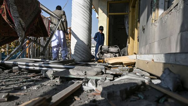 Residents inspect a damaged house after several rockets landed Saturday in Afghanistan