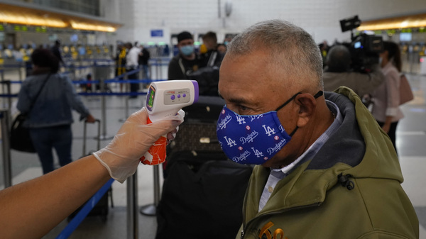 A traveler gets his temperature checked while waiting in line to check in at Los Angeles International Airport on Monday. About 1 million Americans a day packed airports and planes over the weekend even as coronavirus deaths surged across the U.S. and public health experts begged people to stay home and avoid big Thanksgiving gatherings.