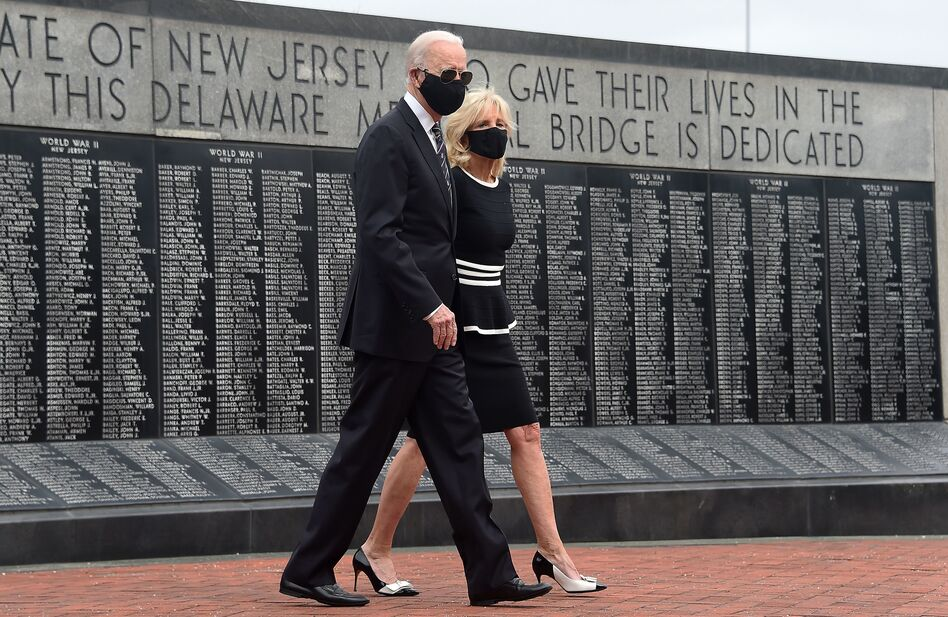 Joe Biden and his wife, Jill Biden, wear masks as they mark Memorial Day. The president-elect has consistently worn masks amid the pandemic, and he's already talking to governors about trying to implement a national mask mandate. (Olivier Douliery/AFP via Getty Images)