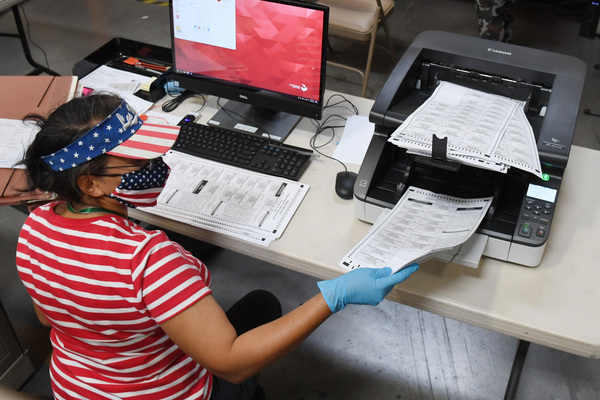 An election worker scans mail-in ballots at the Clark County Election Department last month in North Las Vegas, Nev.