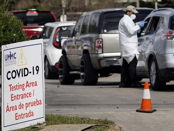 A healthcare worker processes people in line at a United Memorial Medical Center COVID-19 testing site on Nov. 19, in Houston. Texas is rushing thousands of additional medical staff to overworked hospitals as the number of hospitalized COVID-19 patients increases.