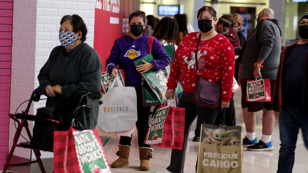 Black Friday shoppers wearing face masks wait in line to enter a store at the Glendale Galleria in Glendale, Calif., on Friday.