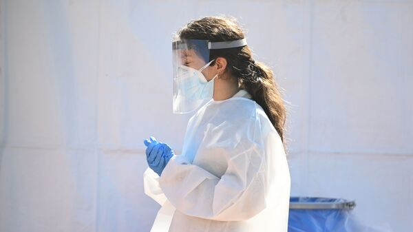 A healthcare worker is seen at a walk-up COVID-19 testing site on Nov. 24 in San Fernando, Calif.