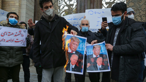 Iranian protesters burn images of President Trump and President-elect Joe Biden during a rally in front of the foreign ministry Saturday in Tehran. Iranian leaders have blamed Israel and its close ally, the U.S., for the assassination of a top Iranian nuclear scientist.
