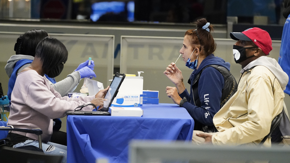 Travelers self-test for the coronavirus at a mobile testing site at New York City's Penn Station in the days leading up to Thanksgiving. The U.S. is currently seeing record hospitalizations for COVID-19, and health experts fear more surges are on their way. (Mary Altaffer/AP)
