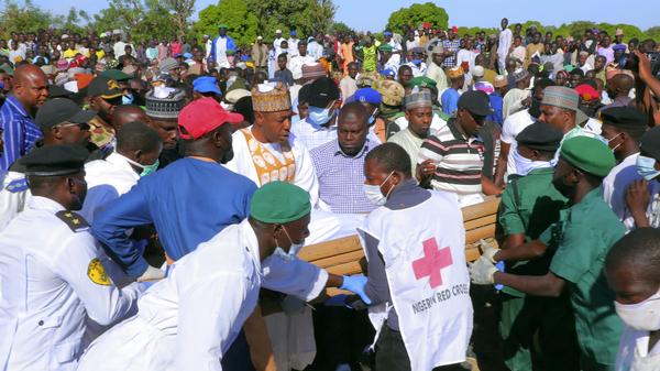 La gente asiste a un funeral por los muertos por presuntos militantes de Boko Haram en Zabarmari, Nigeria, el domingo.  Las autoridades dicen que hombres armados en motocicletas mataron al menos a 70 agricultores de arroz y pescadores mientras cosechaban cultivos en el estado norteño de Borno.