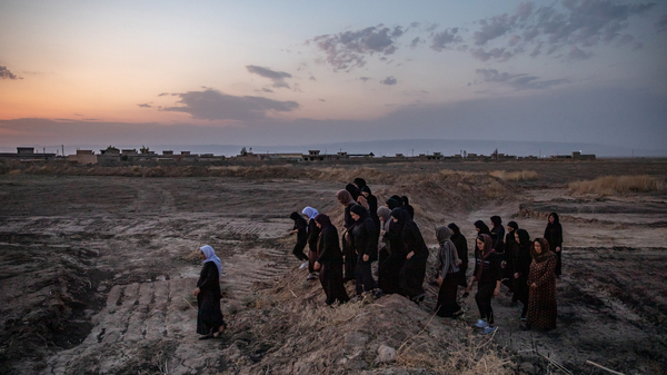 Survivors of the ISIS genocide of Yazidis walk to mass graves near the village of Kocho, northern Iraq, in August 2019, on the fifth anniversary of the massacre that killed most of the men and older boys in the village.