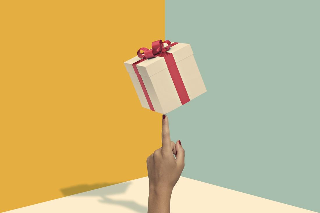 Woman hand balancing present box on index finger