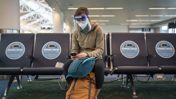 A traveler waits for a flight at Portland International Airport last week in Oregon. Public health experts say it
