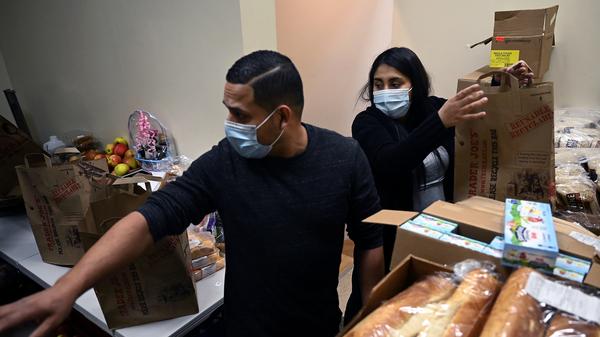 Ingmar Riveros and Peruvian refugee Xiomy De la Cruz distribute food from a store basement last month in Hartford, Conn.