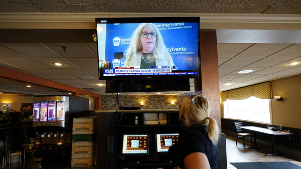 A waitress in South Philadelphia watches a television briefing by Pennsylvania