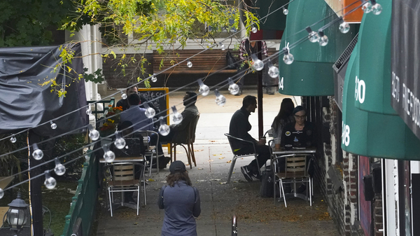 Customers sit outside a restaurant offering outdoor service in New York in October. A new survey shows that tipped service workers are facing a marked increase in harassment during the pandemic.