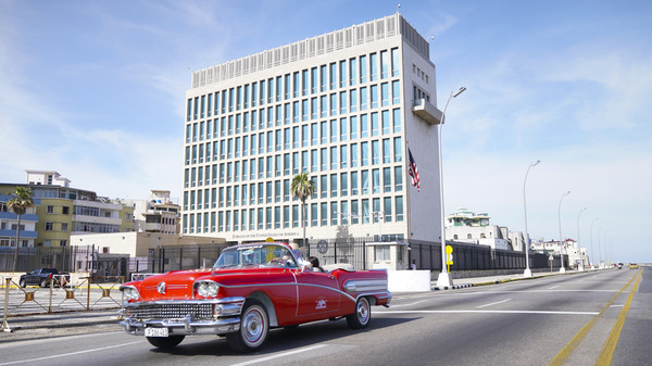 A car drives past the U.S. Embassy in Havana in 2019. Dozens of Americans working at U.S. diplomatic missions in Cuba and China have suffered from ailments that included headaches, balance problems and memory loss in recent years.