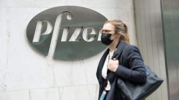 A woman wearing a face mask walks past a Pfizer