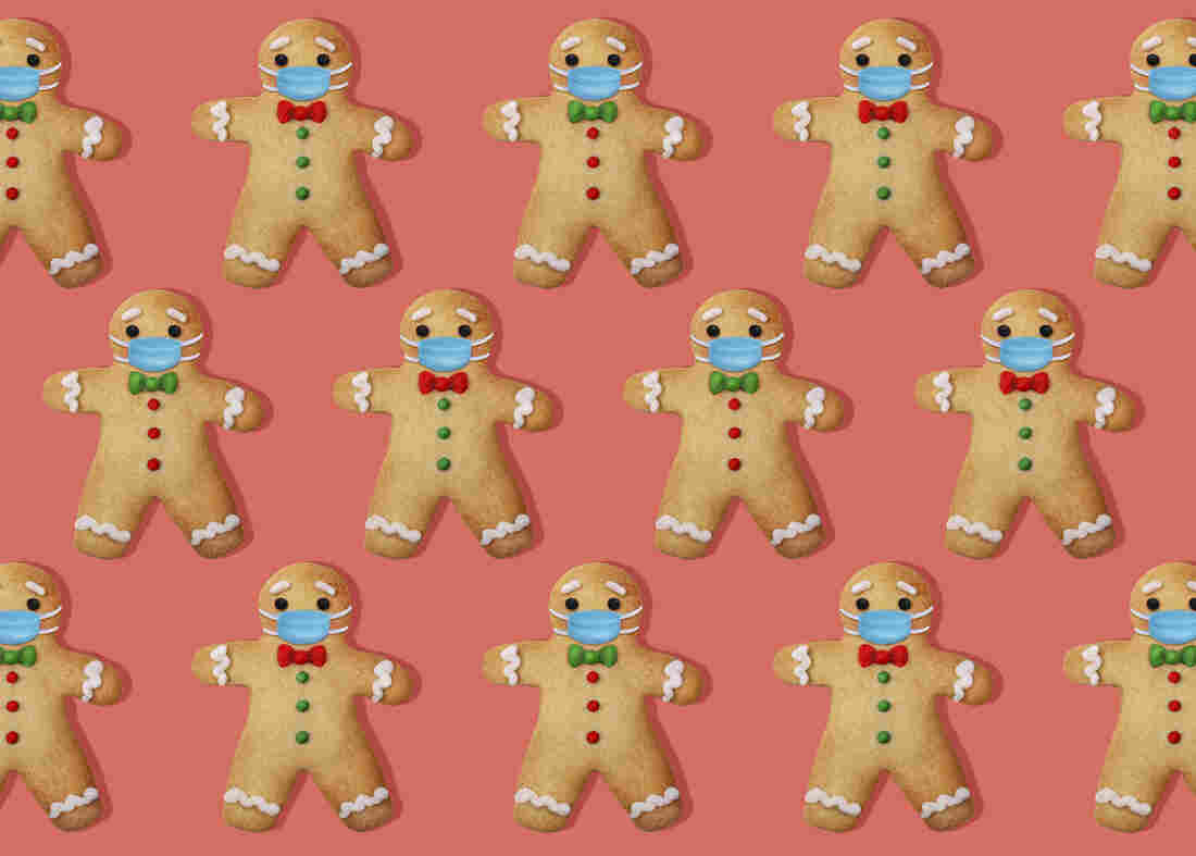 Gingerbread man cookies with surgical mask on pink background.