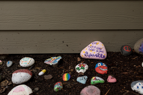 """Painted rocks sit outside Sarah McSweeney's group home in Oregon City, Ore., on Nov. 24, 2020. McSweeney's housemates painted a rock to read """"The World Just Lost Some Sparkle"""" in pink and purple after McSweeney's death."""