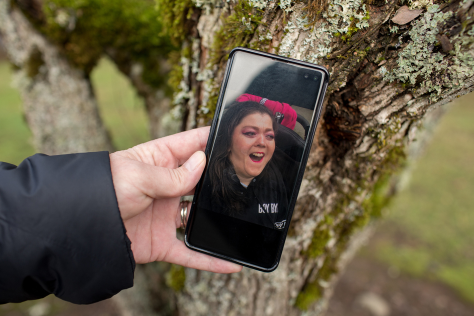 """Kimberly Conger, Sarah McSweeney's nurse at her group home, shows a photo of McSweeney on her phone. She says McSweeney was outgoing and fun: """"She absolutely adored going into malls and getting her makeup done and getting her hair done."""" (Celeste Noche for NPR)"""