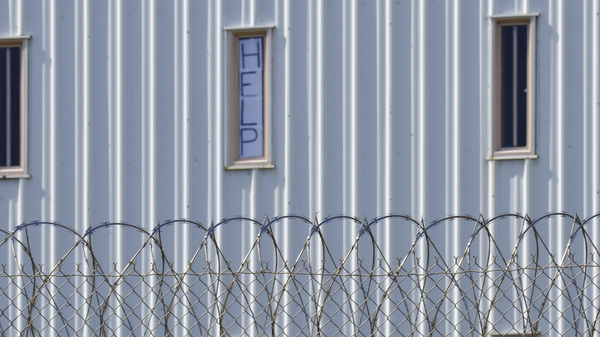 "A sign that reads, ""HELP,"" is posted in the window of an inmate cell during a tour with state officials at Holman Correctional Facility in Atmore, Ala., on Oct. 22, 2019. The Justice Department filed a lawsuit this week against Alabama over conditions in its prisons."