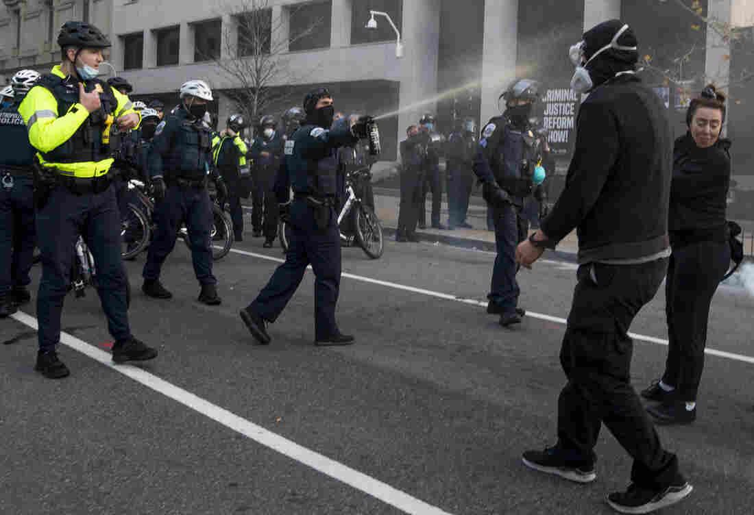 Police spray a counterprotester during a confrontation near Black Lives Matter Plaza.
