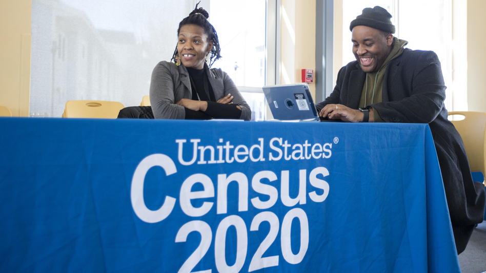 Chris Worrell jokes with Teresa Jefferson while applying for a 2020 census job in Boston in February before the COVID-19 pandemic. Based on government records, the Census Bureau estimates the U.S. population has grown by as much as 8.7% since 2010. (Blake Nissen/The Boston Globe via Getty Images)